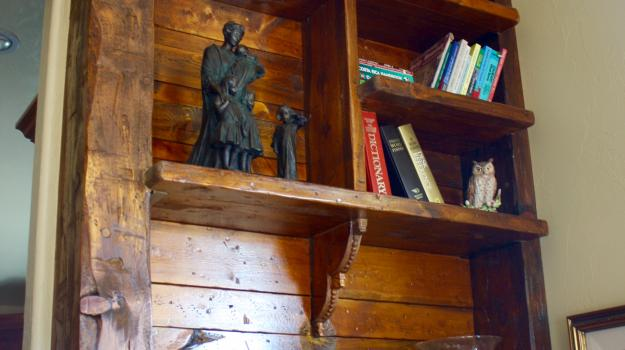 Custom pinewood shelving given a reclaimed look with hand-carved features.